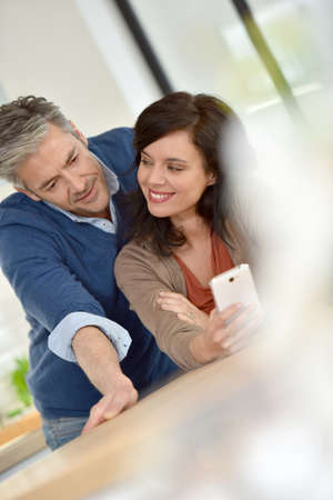middleaged: Middle-aged couple looking at message on smartphone Stock Photo