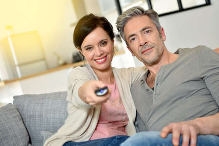 middleaged: Middle-aged couple at home watching television Stock Photo