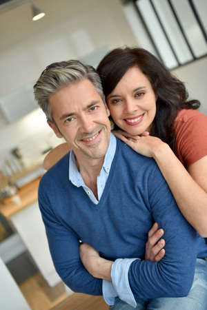 couple relaxing: Portrait of middle-aged couple enjoying new home Stock Photo