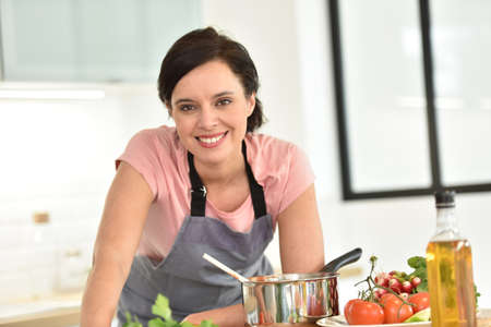 dark haired woman: Portrait of beautiful woman cooking in home kitchen
