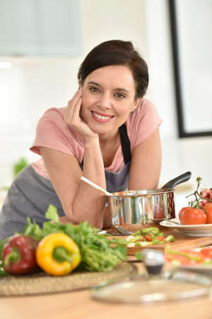 dark haired: Portrait of beautiful woman cooking in home kitchen