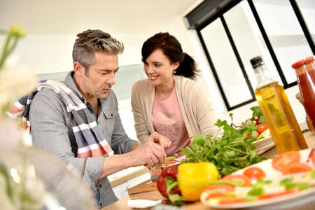 middleaged: Middle-aged couple having fun cooking together