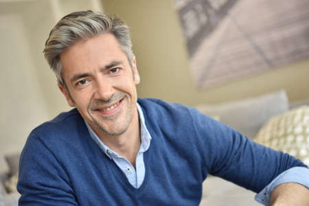 attractive couch: Portrait of smiling handsome man with grey hair