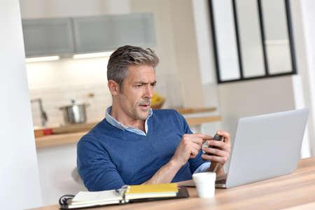 trabajando en casa: Hombre que trabaja desde su casa-oficina con el ordenador portátil Foto de archivo