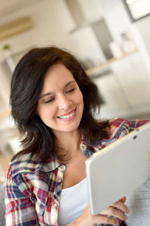websurfing: Cheerful woman at home websurfing with digital tablet Stock Photo