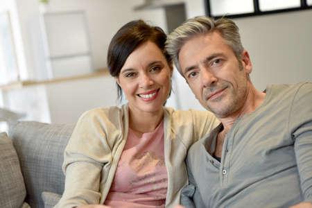 hombres maduros: pareja de mediana edad en su casa viendo la televisión
