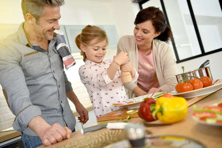family meal: Parents with child cooking together at home