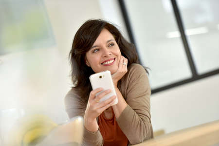 websurfing: Middle-aged woman websurfing with smartphone
