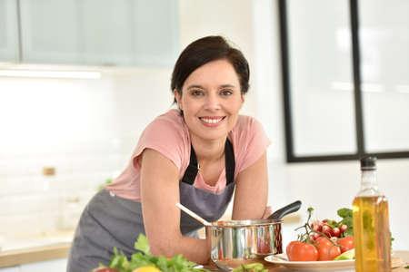 Retrato de la hermosa mujer que cocina en la cocina casera