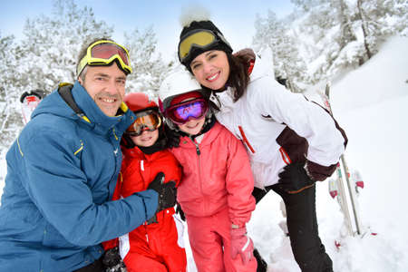 snowy mountain: Portrait of happy family of skiers in snowy mountain