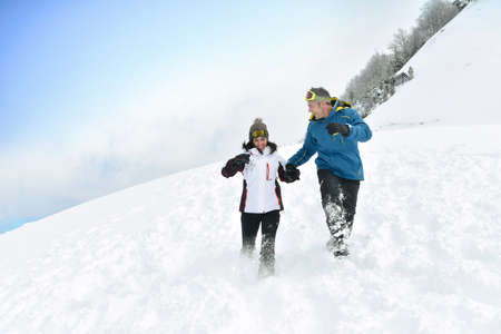 a slope: Couple having fun running down slope Stock Photo