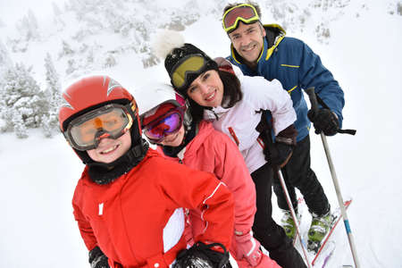 Family of four skiing down slope
