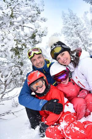 Ritratto di famiglia felice di sciatori in montagna innevata