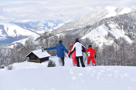 log cabin in snow: Family running down slope in snowy mountains Stock Photo