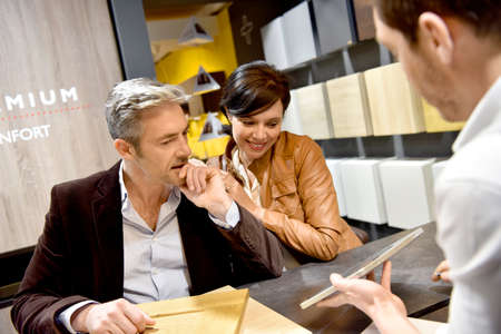 furniture store: Couple with salesman in kitchen furniture store Stock Photo