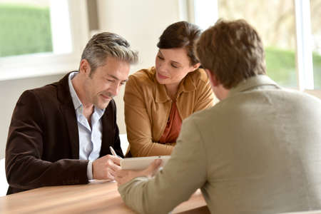 realestate: Mature couple signing documents in real-estate agency Stock Photo