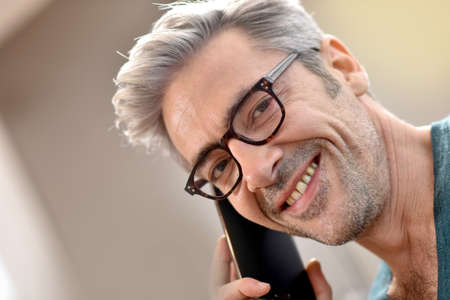 45 years old: Mature handsome man with eyeglasses talking on phone Stock Photo