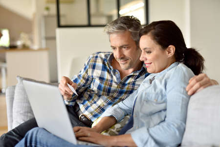 websurfing: Couple in sofa websurfing and shopping on internet Stock Photo