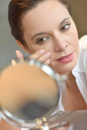woman mirror: Middle-aged woman looking at mirror