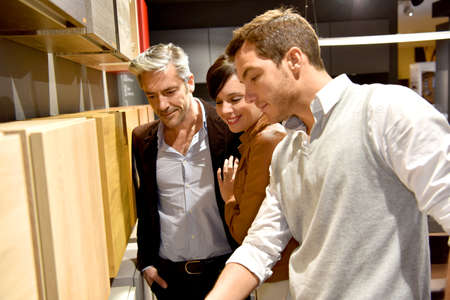 kitchen furniture: Couple with salesman in kitchen furniture store Stock Photo