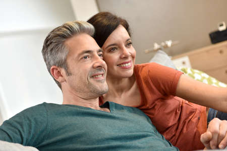 adult entertainment: Middle-aged couple in sofa watching tv