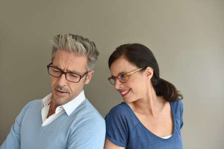 middleaged: Middle-aged couple with eyeglasses on beige background