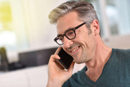 40 45: Mature handsome man with eyeglasses talking on phone Stock Photo