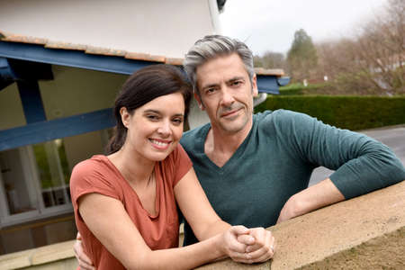 couples outdoors: Middle-aged couple standing in front of new home