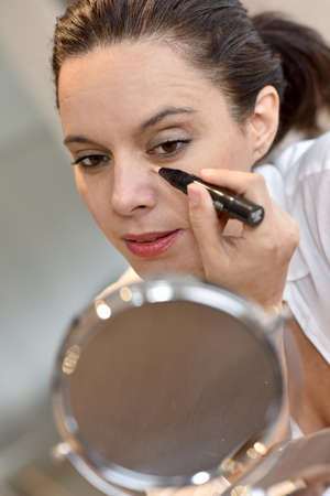 beautycare: Middle-aged woman applying eye concealer in front of mirror Stock Photo