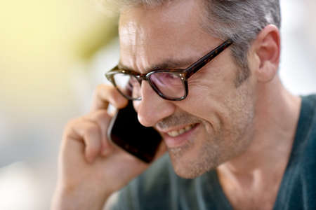 40 to 45 years old: Mature handsome man with eyeglasses talking on phone Stock Photo