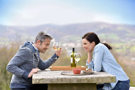 couple nature: Couple cheering with wine sitting in courtyard