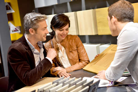 Couple with salesman in kitchen furniture store Standard-Bild