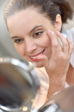 eye cream: Middle-aged woman looking at mirror