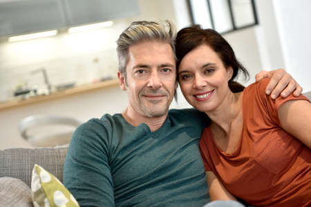 middleaged: Middle-aged couple relaxing together in sofa