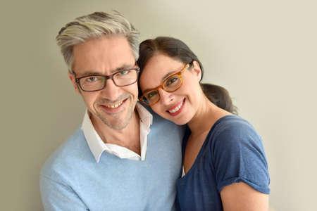 pareja de mediana edad con gafas en el fondo beige