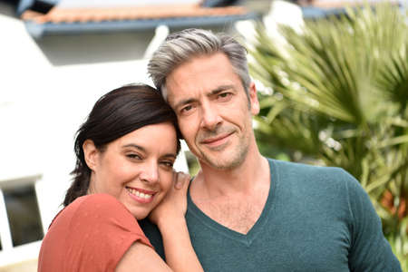 fourties: Middle-aged couple standing in front of new home