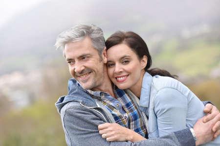 pareja abrazada: Alegre pareja de mediana edad que abarca fuera Foto de archivo