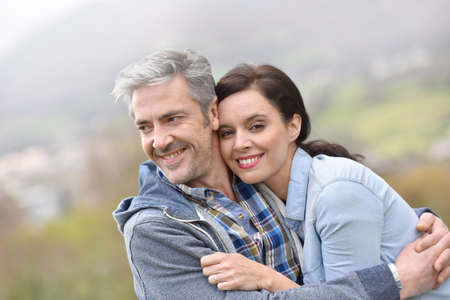 embracing couple: Cheerful middle-aged couple embracing outside