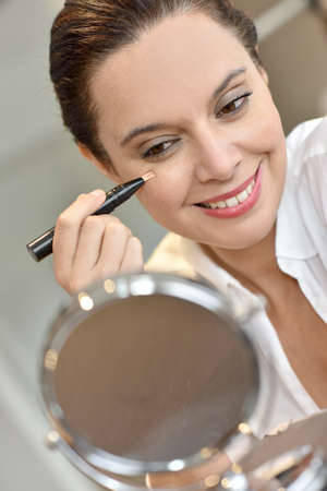concealer: Middle-aged woman applying eye concealer in front of mirror Stock Photo