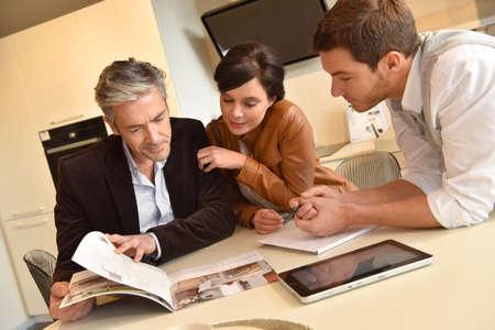 Couple choosing kitchen furniture and getting quotation