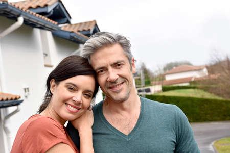 Echtpaar van middelbare leeftijd staan voor nieuwe huis Stockfoto