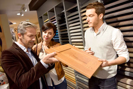 home improvement store: Couple with salesman in kitchen furniture store Stock Photo