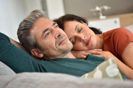 tenderness: Middle-aged couple resting together in sofa