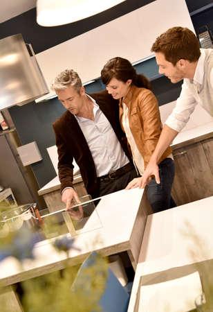 kitchen furniture: Kitchen furniture salesman giving advice to couple