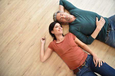Vue de dessus d'un couple allongé sur plancher en bois Banque d'images