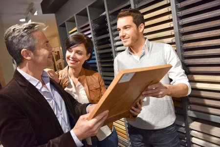Couple with salesman in kitchen furniture store 스톡 콘텐츠