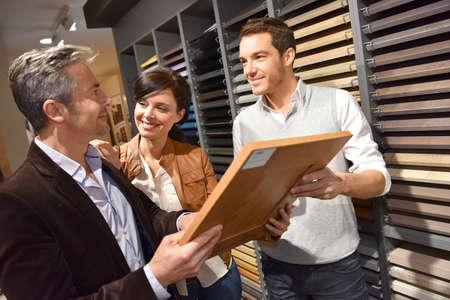 Paar met verkoper in keukenmeubilair winkel Stockfoto - 54121025
