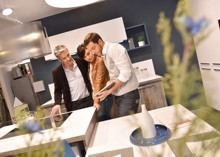 Kitchen furniture salesman giving advice to couple