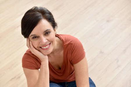 upper floor: Portrait of beautiful woman sitting on wooden floor Stock Photo