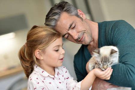 niños rubios: Papá con pequeño gato chica de mascotas en el hogar Foto de archivo